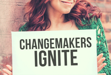 changemakers ignite, woman standing holding sign