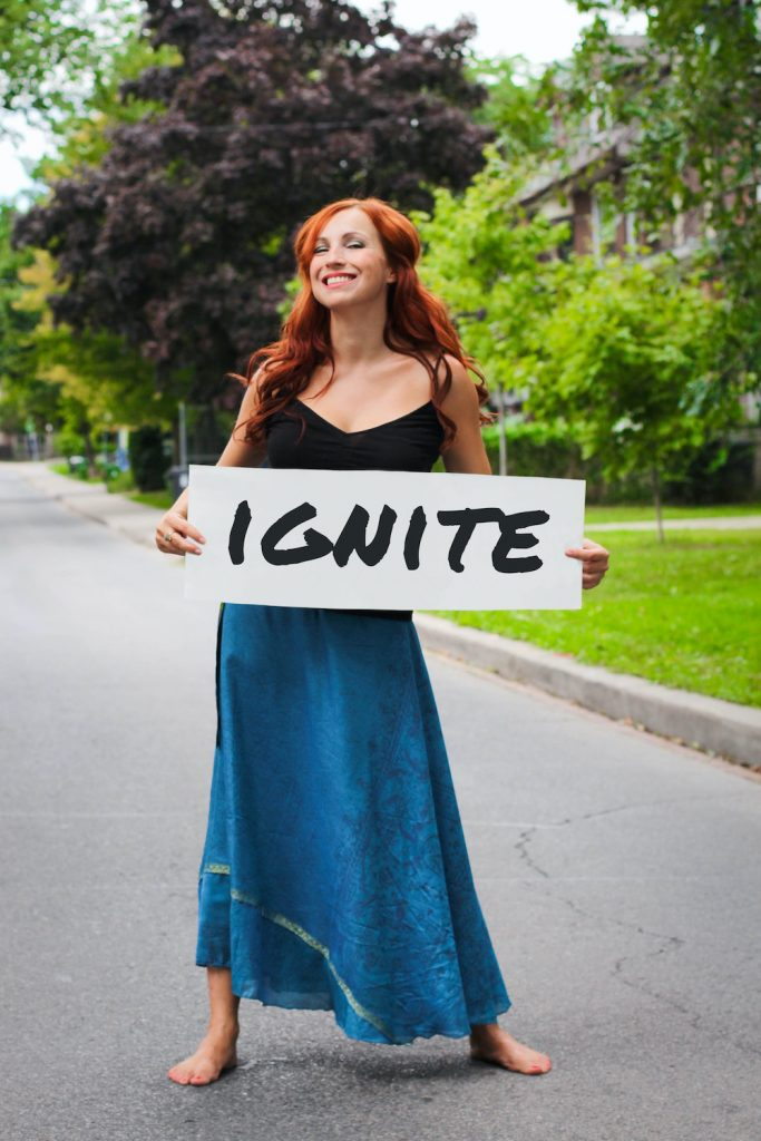 Kimberly Carroll, woman standing in street holding Ignite sign